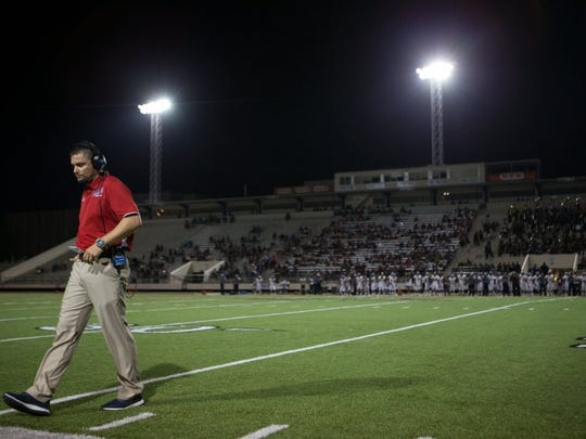 COURTNEY SACCO/CALLER-TIMES Veterans Memorial head coach Cody Simper walks off the field after talking to the referee during the third quarter of their game against La Feria at Buccaneer Stadium on Friday, Sept. 9, 2016.