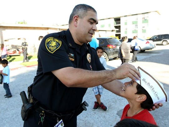 Caller-Times File Assistant Chief Mike Alanis gives Roman Yanez, 9, his paper hat at a National Night Out event in October 2014.