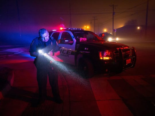 COURTNEY SACCO/CALLER-TIMES A Corpus Christi police officer stands in dense fog, filling out paperwork to impound a vehicle in January. Police data indicates a high volume of domestic violence calls in the S. Port Avenue, Ayers Street and Tarlton Street area.