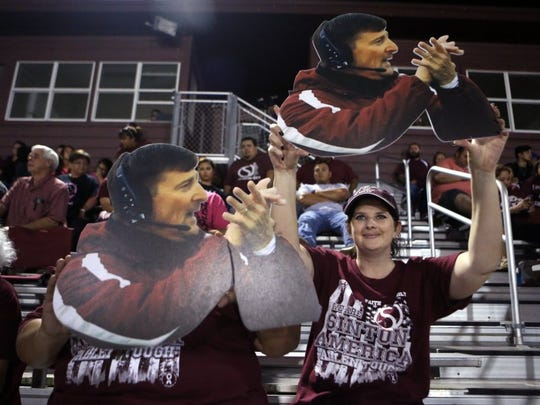 Rachel Denny Clow/Caller-Times Chrissy Sample (right) and another fan hold up a Fathead of Sinton head coach Tom Allen during the Pirates' game against Aransas Pass on Friday. The community has rallied around the coach as he battles Multiple Systems Atrophy.
