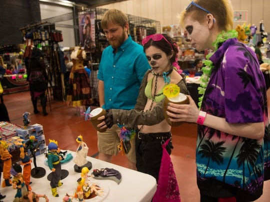 Charlie Blalock/ Special to the Caller-Times Kyle Redy (from left), Katelynn Favela and Sheila Qsa look at toys from Best Anime Shop at Realms Con on Saturday, Oct. 1, 2016, at American Bank Center.