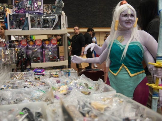 Charlie Blalock/ Special to the Caller-Times Alysha Garza, dressed as Opal from Steven Universe, looks at toys from Custom Toys of San Antonio at Realms Con on Saturday, Oct. 1, 2016, at American Bank Center.