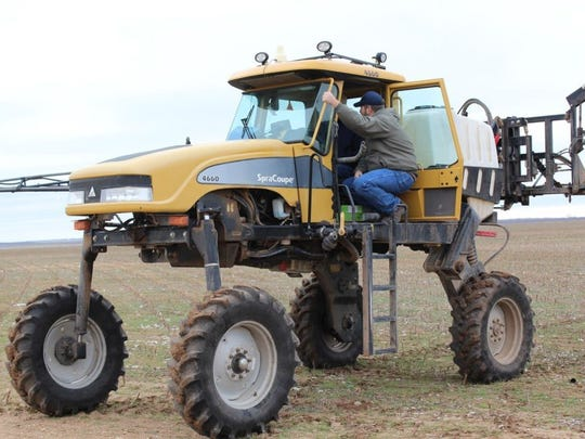 Kenneth Halfmann boards a tractor on his farm.