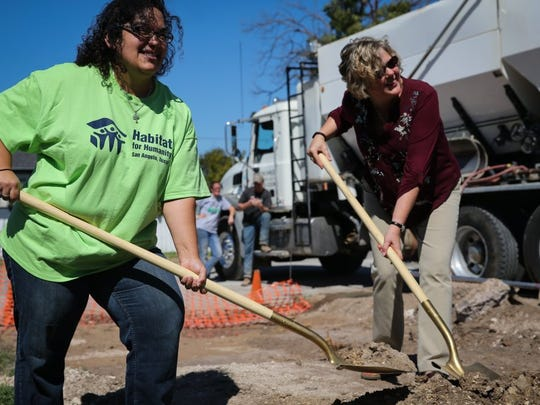 Joanna Garcia (left), homeowner, and Libby Mims, Habitat for Humanity board member, shovel up dirt at the groundbreaking for Habitat for San Angelo's 78th home. Habitat volunteers build houses in partnership with people in need of decent affordable housing.