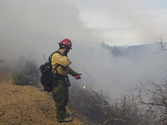 File photo - Joedan Pearsall, a fire engine operator with the Shasta Trinity National Forest, works a prescribed burn in 2016 above Lakehead.