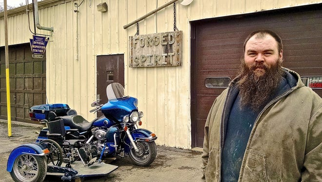 """In this Dec. 30, 2015 photo, Brian Mahaney of Forged Spirit Garage shows off a wheelchair accessible sidecar in Bradford, Pa. Mahaney and his wife, Michelle, started """"Forged Spirit Garage"""" this past summer with the intent to develop a wheelchair accessible sidecar, which offers what he calls """"two-wheel therapy."""" (Josh Hatcher/The Bradford Era via AP)"""