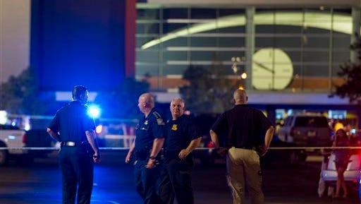 Law enforcement personnel stand near a police line at The Grand Theatre following a deadly shooting in Lafayette, La., Thursday, July 23, 2015. (Paul Kieu/The Daily Advertiser via AP)
