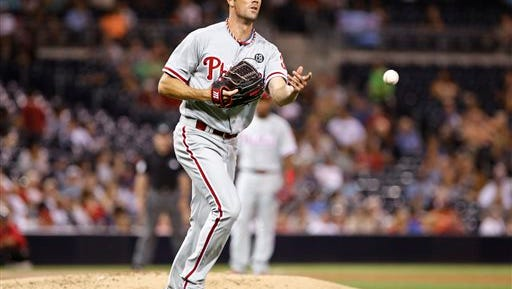 Philadelphia Phillies starting pitcher Cole Hamels throws over to first base to make the out on a short grounder by San Diego Padres' Abraham Alomonte  during the third inning of a baseball game Wednesday, Sept. 17, 2014, in San Diego. (AP Photo/Don Boomer)