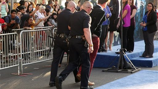 """Journalist Vitalii Sediuk is walked off carpet in handcuffs after allegedly attacking Brad Pitt at the world premiere of """"Maleficent"""" at the El Capitan Theatre Wednesday  in Los Angeles."""
