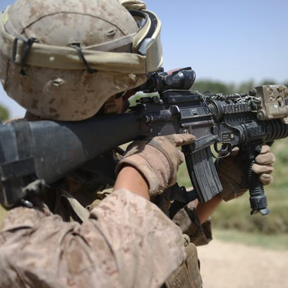 A US Marine from Kilo Company of the 3rd Battalion 8th Marines Regiment looks through his scope while conducting a patrol at the Kalinoum village, west of Garmser, Helmand Province on June 23, 2012. The US-led war in Afghanistan has cost the lives of around 3,000 U.S. and allied troops, seen thousands of Afghans killed and cost hundreds of billions of dollars. AFP PHOTO / ADEK BERRY        (Photo credit should read ADEK BERRY/AFP/GettyImages)