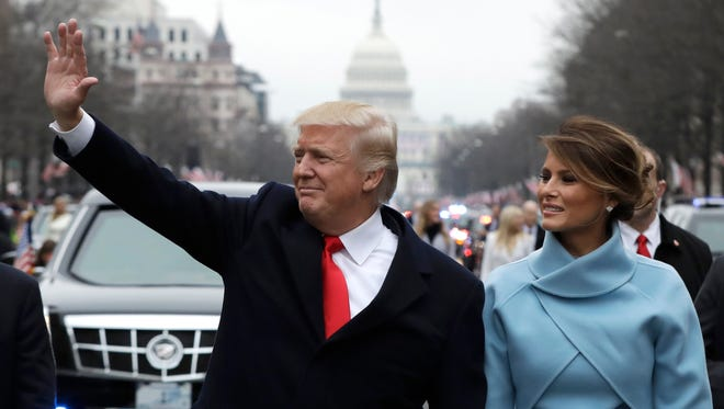 President Trump waves as he walks with first lady Melania Trump during the Inaugural Parade.