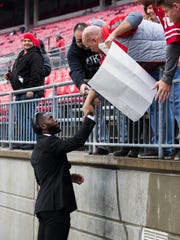 Ohio State quarterback J.T. Barrett hands a lucky buckeye to a fan as the Buckeyes head for their locker room inside Ohio Stadium prior to Saturday's game.