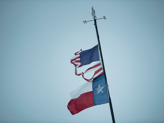 A Texas and U.S. flag fly as rain from Hurricane Henry
