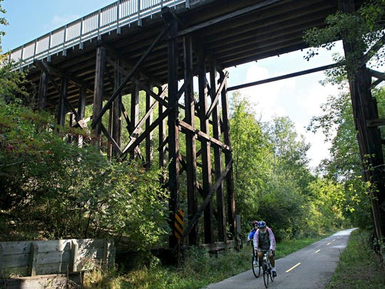 A pair of cyclists ride the Glacial Drumlin State Trail
