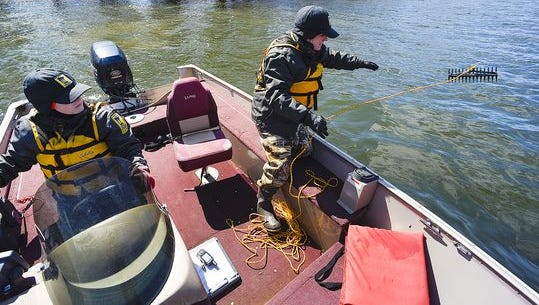 Courtney Millaway, left, a Sauk Rapids-based natural resources specialist with the Minnesota Department of Natural Resources, pilots the boat for Chris Jurek, aquatic invasive species specialist, as she collects samples of starry stonewort April 4 on Lake Koronis.