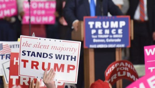 """A supporter at a Trump rally Saturday night in Denver holds a """"silent majority"""" sign as the candidate speaks. Many Trump supporters felt the depth of his support wasn't accurately reflected by mainstream media coverage of the race."""