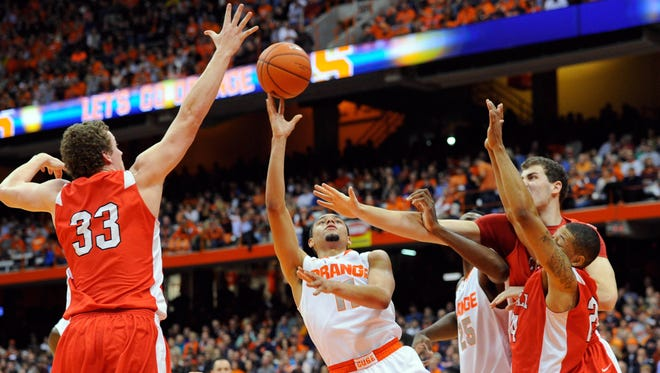 Syracuse Orange guard Tyler Ennis (11) takes a shot between Cornell Big Red forward Dwight Tarwater (33) and guard Devin Cherry (24) during the first half.