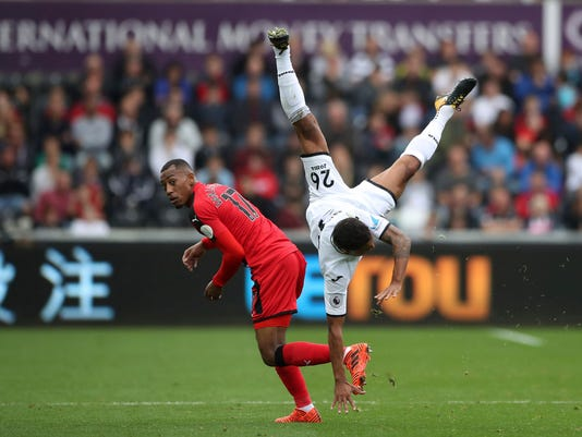 Swansea City's Kyle Naughton, right, is upended to land on his head as he clashes with Huddersfield Town's Rajiv van La Parra, during their English Premier League soccer match at the Liberty Stadium in Swansea, England, Saturday Oct. 14, 2017. (Nick Potts/PA via AP)