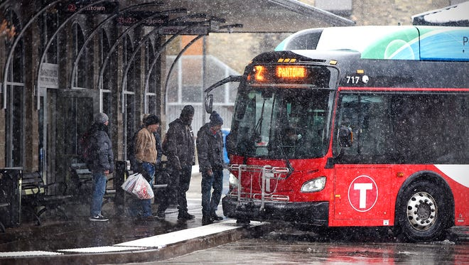 People board a MetroBus at the downtown St. Cloud transit center as snow falls Wednesday afternoon.