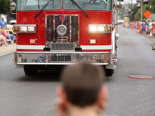 A young boy covers his ears to shield from the loud sirens of the Williamsburg Fire Department. (File photo)
