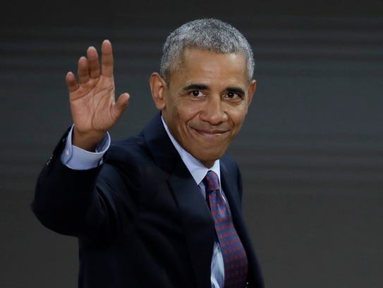 Former president Barack Obama waves as he leaves the