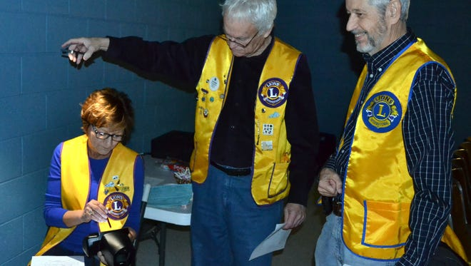 Morganfield Lions Club members Susan Girten, from the left Matt Buckman and Dr. Bill Tapp, prepare the vision screening camera.