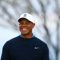 Tiger Woods smiles during a practice round for the Waste Management Phoenix Open at TPC Scottsdale. Last week, while visiting his girlfriend Lindsey Vonn, he had a tooth knocked out by a camera.