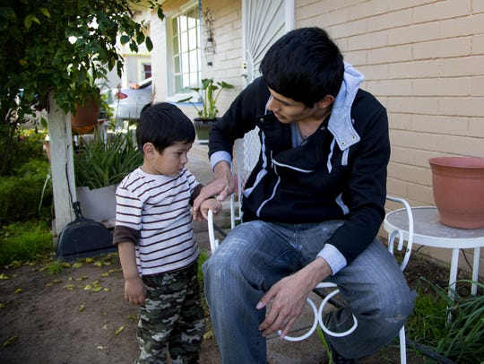 Gerson Gonzalez, 25, talks to his 2-year-old son, Eli,