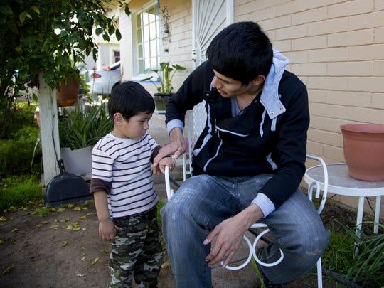 Gerson Gonzalez, 25, talks to his 2-year-old son, Eli,