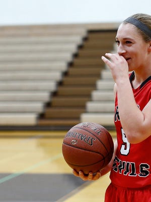 Green Bay East senior Jaida Reynen, shown after scoring her 1,000th point in basketball, earned unanimous first-team all-Bay Conference honors in volleyball, basketball and softball.