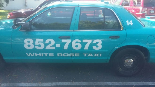A parked White Rose taxi.