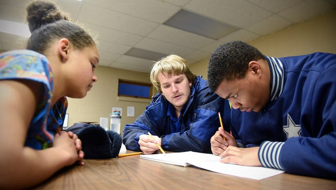 Kevin Duffy, center, helps Aliyah Price, right and Tehron Buffman with math homework Friday, Jan. 20, at Promise Neighborhood of Central Minnesota in St. Cloud.