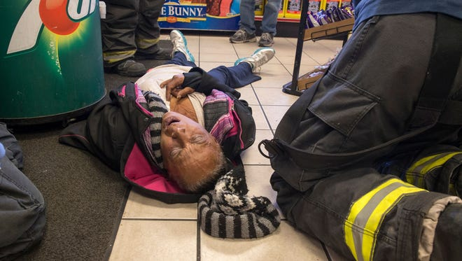 A woman, who had passed out in a convenience store, is suffering from tell-tale signs of the local street drug KD, made from bug killer, in Indianapolis, in November. The drug, variously called KD, Katie, or Zombie, is made from something smokeable like synthetic marijuana, or simply a cigarette, and doused with bug spray that is dried, then smoked. It gives a temporary high, and the long-term effects aren't known.