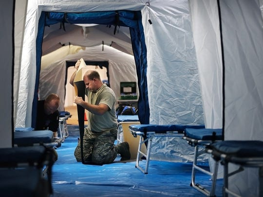 Staff Sgt. Corey Wampler (right) and Trent Harris with the Health Department finish setting up a triage area for Houston hospital evacuees at the National Guard hangar at the airport. If activated, the triage would assess patients flown to Memphis, then direct them to area hospitals that have the facilities and vacant beds to handle the incoming patients.