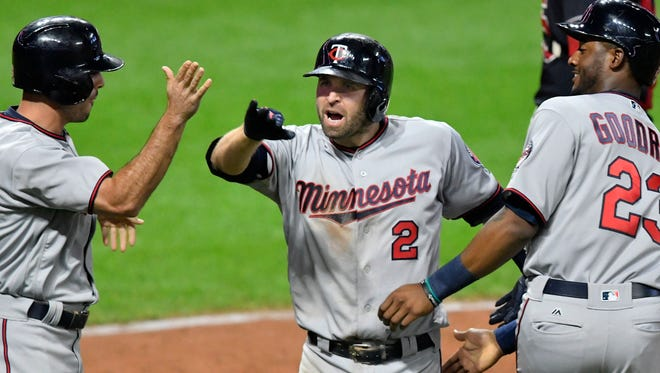 Minnesota Twins second baseman Brian Dozier (2) celebrates with center fielder Zack Granite (8) and third baseman Niko Goodrum (23) after hitting a three-run home run against the Cleveland Indians in the eighth inning at Progressive Field.