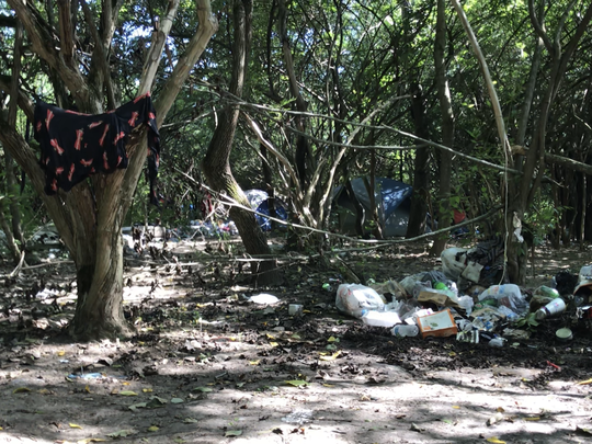 Trash is skewed across the ground inside this homeless camp in Hamilton.