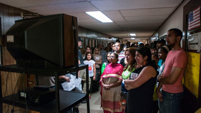 """In the 2015 photo, a large crowd was gathered at the Clifton Board of Education where they held a uniform forum where the public spoke on their opinions of a """"uniform dress code policy"""" for elementary school students. The crowd grew so large that a TV was brought out so people in the hall may watch."""