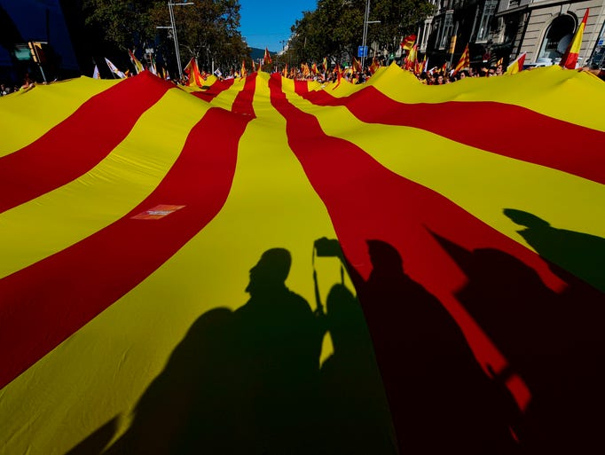 People hold a giant Catalan Senyera flag as protesters