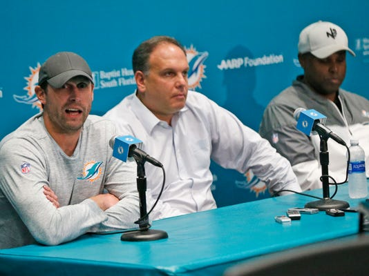 Miami Dolphins head coach Adam Gase, left, answers a question during a news conference with Mike Tannenbaum, center, executive vice president of football operations, and Chris Grier, general manager, at the teams NFL football training camp, Wednesday, Jan. 3, 2018 in Davie, Fla. The three talked about offseason plans in the wake of the team's disappointing 6-10 showing. (AP Photo/Wilfredo Lee)