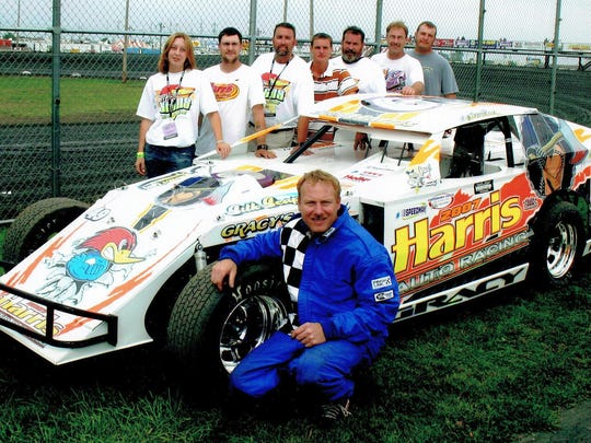 """Local racer Dan Gracyalny poses with his car, lettered by Woody's Signs of Sturgeon Bay, which won the Best Appearing Car award at the IMCA Supernationals at Boone (Iowa) Speedway. Woody's Signs owner Bryan """"Woody"""" Wodack, the longtime promoter of Thunderhill Raceway in Sturgeon Bay, is third from left in the back row."""