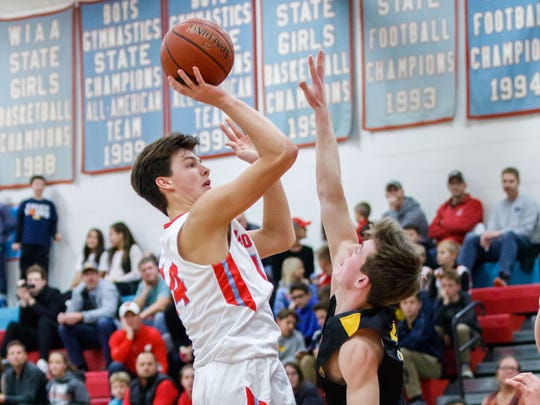Arrowhead sophomore Carter Gilmore (14) elevates for a shot over Kettle Moraine's Graham Held (3) at Arrowhead on Friday, Dec. 1, 2017.