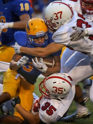 Carmel's #3 Jalen Walker is tackled in first half action during the Center Grove at Carmel High School football game, Friday, September 4, 2015.