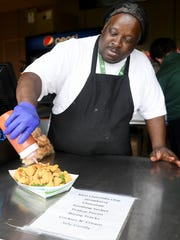 Jackson Generals concessions cook Paul Robinson pours hot sauce onto a catfish poboy sold at the Ballpark at Jackson.
