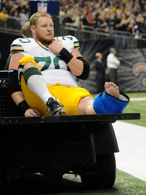 Packers guard T.J. Lang shows his frustration while being carted off the field in the first quarter against the New Orleans Saints.