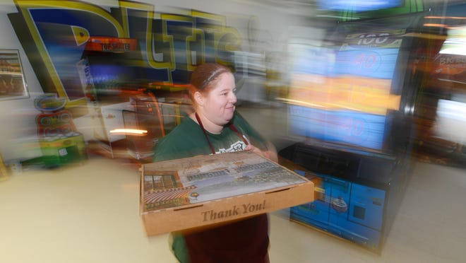 Libby Steer carries a pizza through Blits in Zanesville. Blits is part restaurant and part amusement park, with a full menu and a variety of games for kids and adults to play.