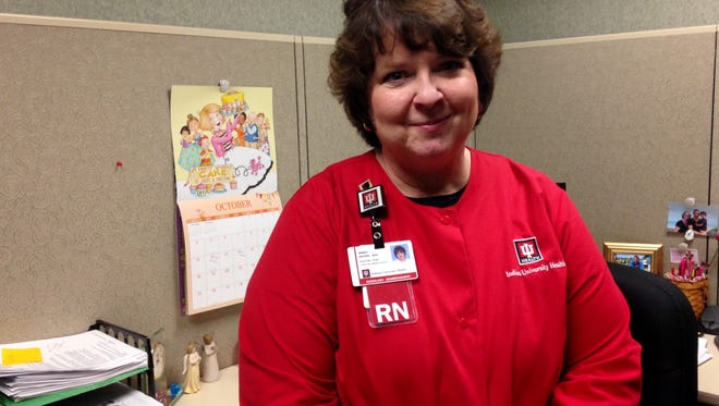 Nancy Brown poses in her officer during breast cancer awareness month. As a nurse navigator for IU Health Ball Memorial Breast Health Services, she is often is the person who tells patients they have cancer.