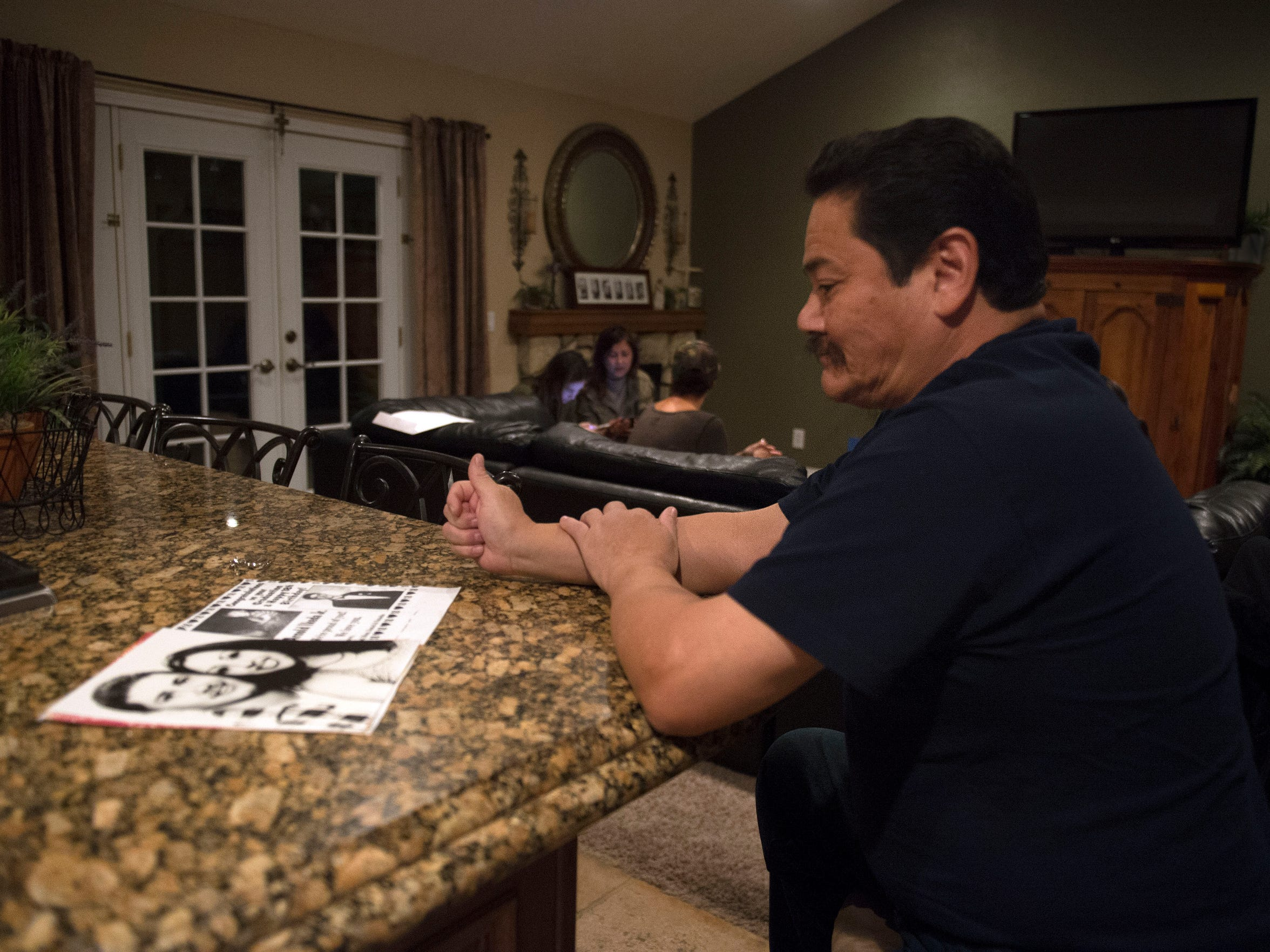 Arnold Ikeda Sr. looks at a photo of his son, Arnold