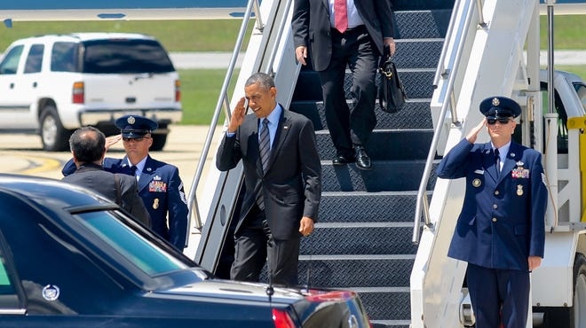 President Barack Obama, followed by Sen. Chris Coons, D-Del., salutes members of the military upon his arrival at New Castle Air National Guard Base in New Castle, Del., Thursday, July 17, 2014.