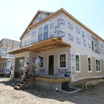 Real estate stagers Deborah Valentino, left, and Jo Anne Eekhof and real estate agent Thomas Hennessy of Houlihan Lawrence look over a modular house on Helena Ave. in Yonkers July 20, 2015. The house is part of Helena Heights, a development of nine modular houses.