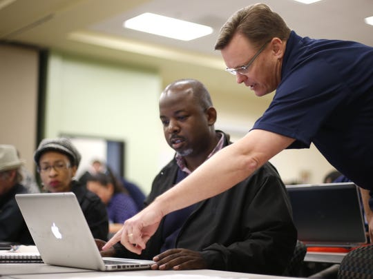 Patrick Holcomebe, right, a trainer at a Google Business Town Hall, helps Ivery Luckey to establish his business' presence online though Google's business pages on Monday, Nov. 30, 2015. The page building helps users find businesses like Luckey's, a contract bus provider called School District Service, when utilizing the search engine to locate local providers.